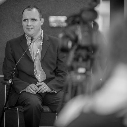 Candid photograph of Paul being filmed whilst giving a presentation. He is seated and is speaking into a microphone